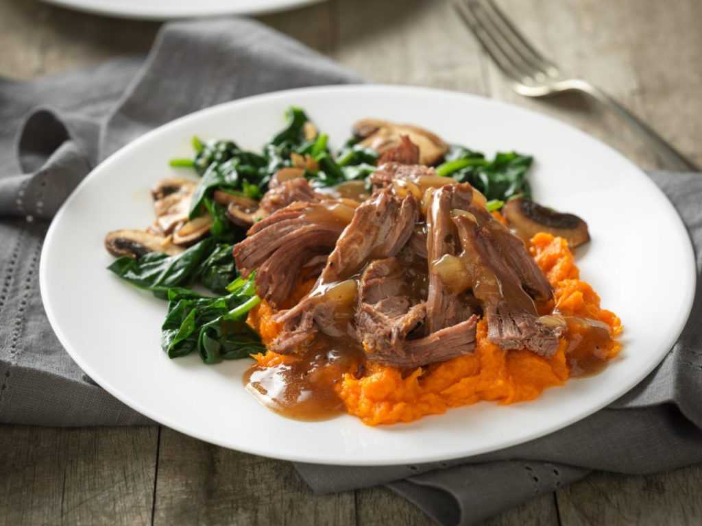 a plated serving of pot roast with maple sweet potatoes and cider gravy